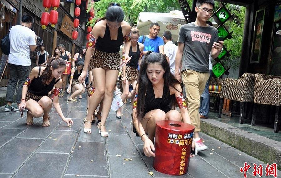 """8月28日,""""豹女郎""""们在锦里古街捡垃圾。当天,40名身着豹纹露背短裙装的性感""""豹女郎""""提着公德移动垃圾桶亮相成都锦里,在锦里古街进行了""""不怕热,不怕苦,公德就学阿不叔""""公德接力活动。中新社发 林峰 摄"""