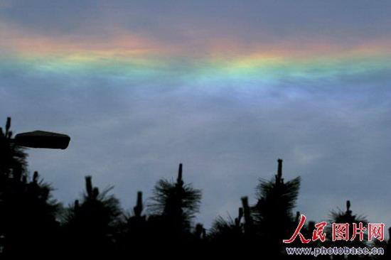 人民网讯 2008年6月14日上午,在山东省青岛市东南方向突然出现一道彩云。   据了解,这道彩云出现在上午10点40分左右,呈直线形状在太阳一侧显得极为亮丽夺目,吸引了众多市民的好奇。据青岛气象局专家(李庆宝)介绍,气象学上称这七色彩环出现在太阳周围的光圈叫日晕,不是坊间传言的地震云,日晕是阳光透过云中的冰晶时发生折射和反射形成的。而冰晶结构的云常常是冷暖空气相遇而生成的云层,随着云层增厚,逐步发展成雨层云(或卷层云),因此晕就往往成为阴雨天气的先兆。(朱武涛)
